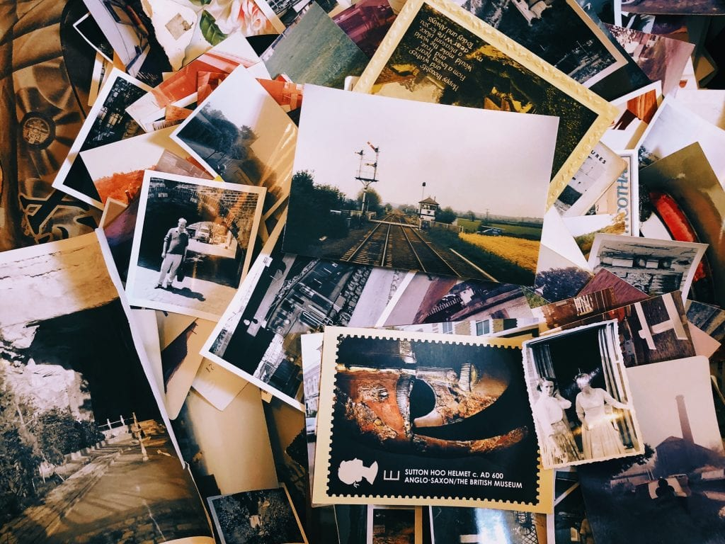 A pile of photographs in a mess on the floor.