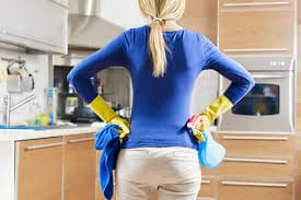 A woemen wearing white pants and blue shirt  holding a blue cleaning cloth and spray bottle