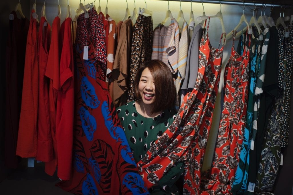 Asian lady surrounded by colorful clothes in her organized closet